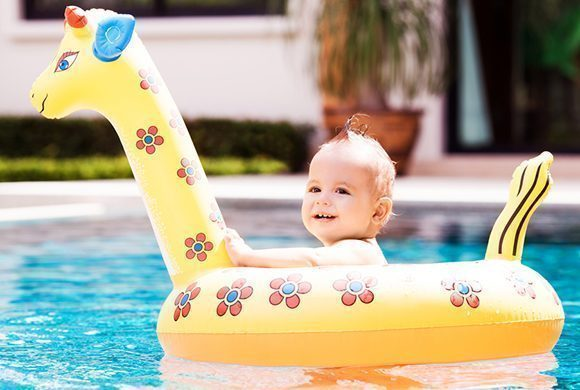 cute one year old baby swimming with a float in the swimming pool